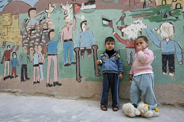 A young Palestinian boy and girl stand near a painted mural in Balata Refugee Camp in the West Bank city of Nablus. (Miriam Alster/Flash90)