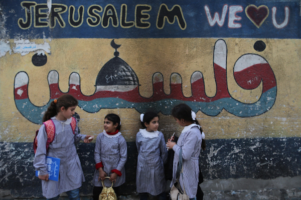 Palestinian school girls stand in front of a mural painted on their school wall in Gaza City on March 13, 2013. (Wissam Nassar/Flash90)
