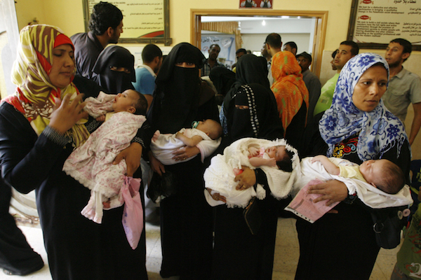 Palestinian women hold their babies, who had been born in shelters during the 2014 Israeli offensive on Gaza, during a ceremony to honor the mothers in an UNRWA center in Rafah refugee camp, in southern Gaza Strip on August 13, 2014. (Abed Rahim Khatib/Flash90)