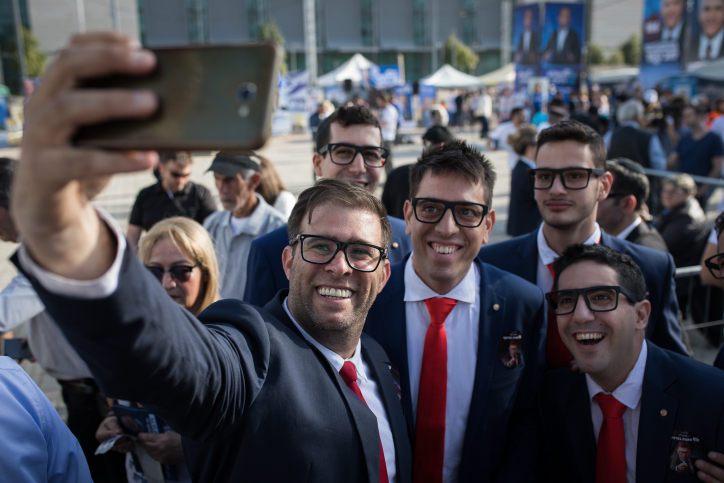 Likud MK Oren Hazan with supporters outside a Tel Aviv polling station during the Likud party primaries, February 5, 2019. (Hadas Parush/Flash90)