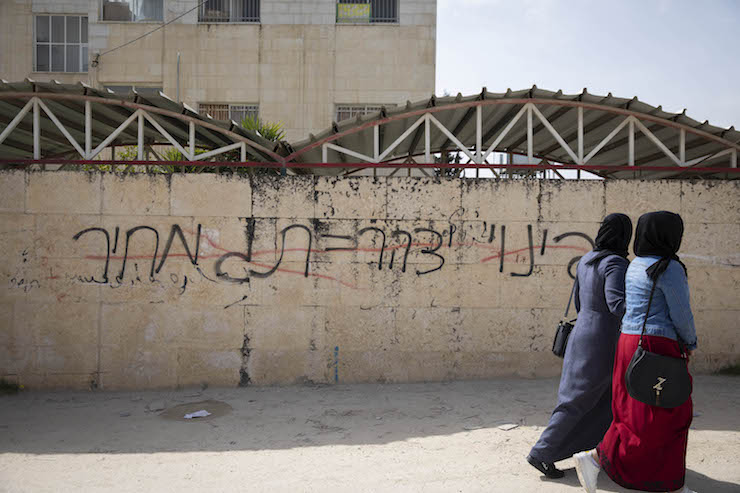 Palestinian women walk by a wall that had been hit by price tag graffiti. The graffiti reads: 'Evacuating Yitzhar = price tag.' (Oren Ziv/Activestills.org)