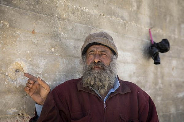Munir Suleiman, fro the Palestinian village of Urif, points the a bullet hole in his home, which was targeted by settlers. 'Sometimes they come down with the army, sometimes the army joins later, after the entire village comes out to defend itself.' (Oren Ziv/Activestills.org)