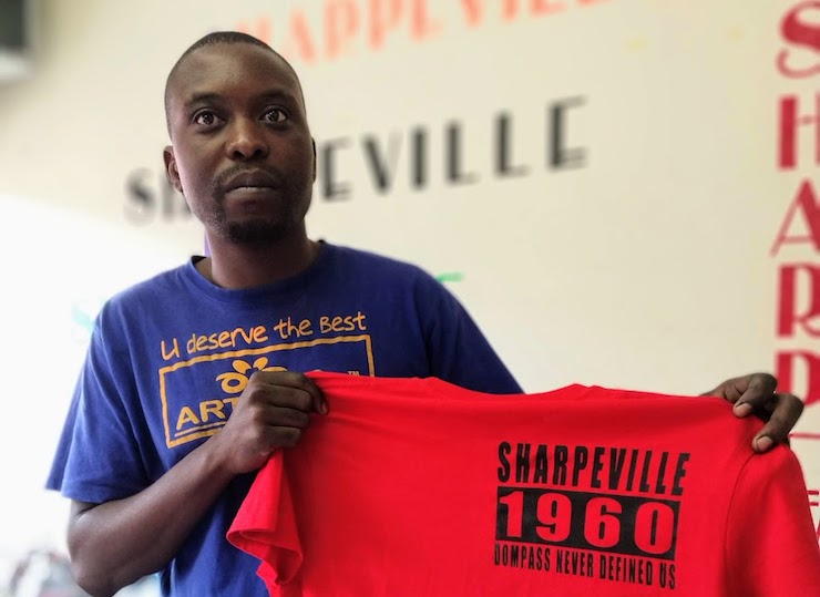 Karabo Mokoena holds one of the shirts produced by Sharpeville Printers and Designs. (Samer Badawi)