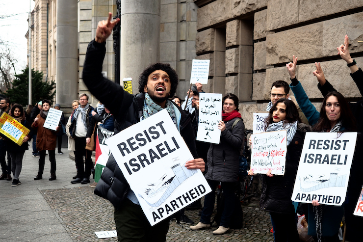 Demonstrators hold signs outside a Berlin courthouse on the opening day of the trial of three BDS activists charged with assault for interrupting an Israeli MK during a lecture in 2017, March 4 2019. (Magda Stefanenco)