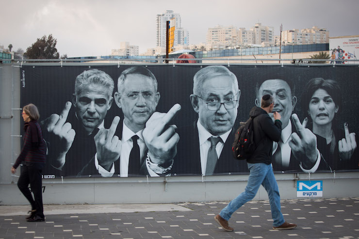 Israelis walk past a campaign billboard in Jerusalem for the Yashar political party, with major politicians seen giving the public the middle finger, March 10, 2019. (Noam Revkin Fenton/Flash90)