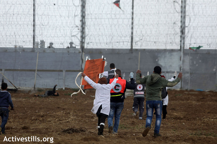 Volunteer medics hold their hands above their heads as they try to reach a wounded protester near the fence, east of Gaza City, March 30, 2019. (Mohammed Zaanoun/Activestills.org)