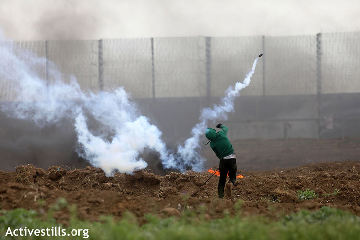 A Palestinian protester throws a tear gas canister back toward Israeli troops positioned along the Gaza fence, east of Gaza City, March 30, 2019. (Mohammed Zaanoun/Activestills.org)