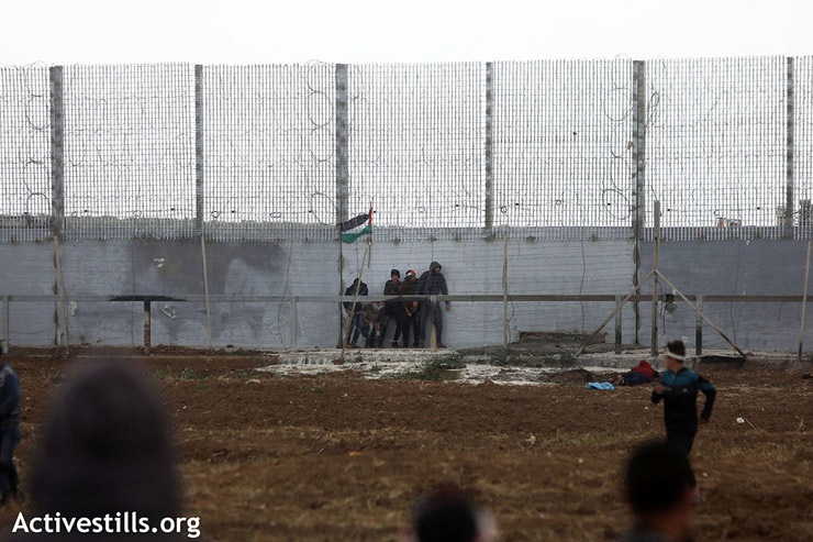 A group of protesters takes cover from Israeli troops as they approach the fence, east of Gaza City, March 30, 2019. (Mohammed Zaanoun/Activestills.org)