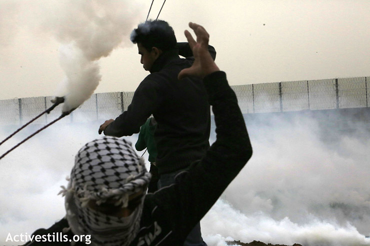 Protesters throw back tear gas canisters toward Israeli soldiers, east of Gaza City, March 30, 2019. (Mohammed Zaanoun/Activestills.org)