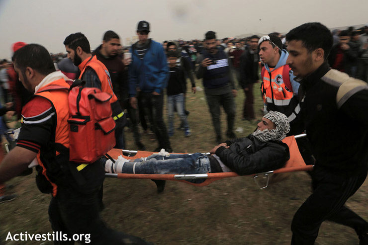 Medics evacuate a wounded protester who was shot in the leg by an Israeli sniper, east of Gaza City, March 30, 2019. (Mohammed Zaanoun/Activestills.org)