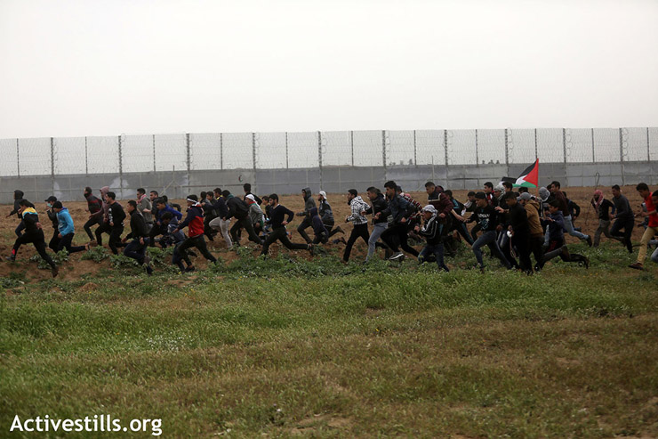 A large group of protesters runs from Israeli sniper fire and crowd control measures, east of Gaza City, March 30, 2019. (Mohammed Zaanoun/Activestills.org)