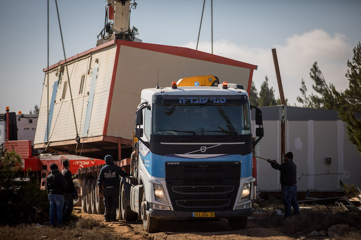 Israeli security forces load a prefabricated home onto a truck during the evacuation of an illegal Israeli settlement, Amona, in the West Bank, January 3, 2019. (Yonatan Sindel/Flash90)