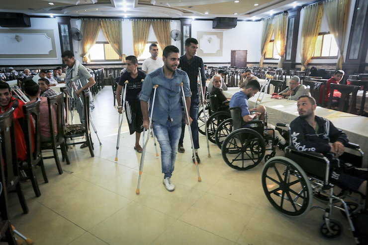 Young Palestinian men who lost their legs after being shot by Israeli snipers in the Great Return March attend an Iftar dinner organized by a charity in Khan Younis, Gaza Strip, June 11, 2018. (Abed Rahim Khatib/Flash90)