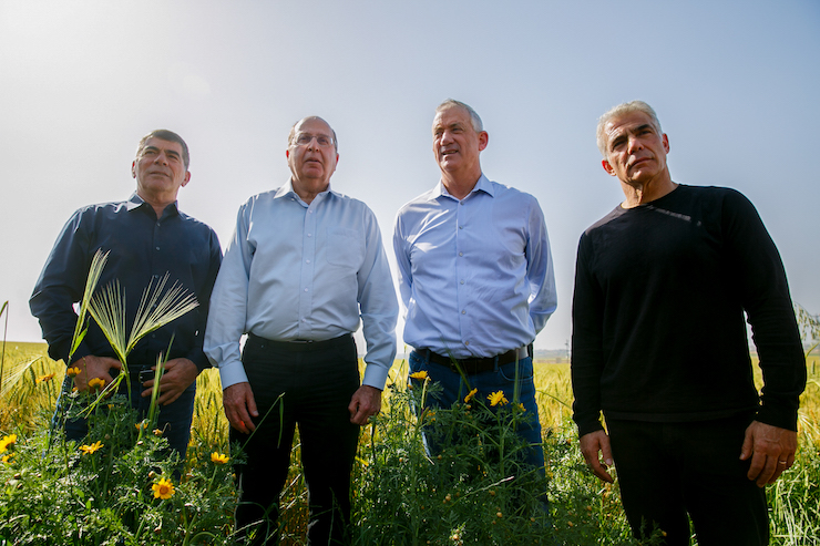 The three generals (and Yair Lapid) who comprise the 'Blue and White' party pose for photos in a field near the Gaza border, March 13, 2019. (Flash90)
