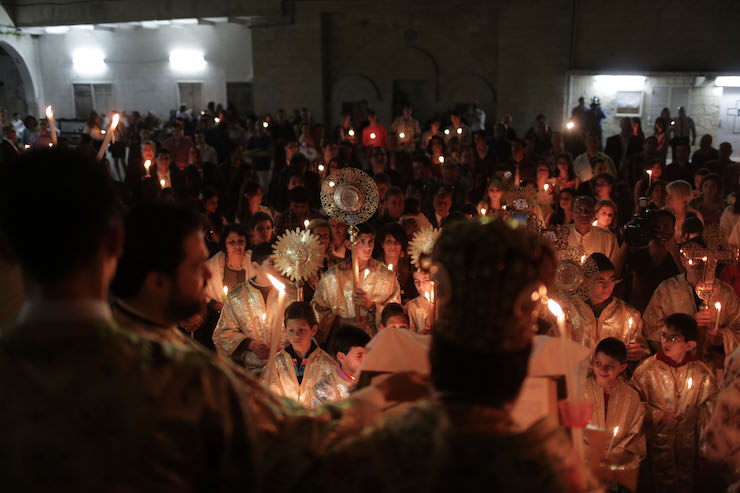 Palestinian Christians hold candles lit by the holy fire, which was delivered from the Church of the Holy Sepulcher in Jerusalem, at the Church of Saint Porphyrius in Gaza City, on April 20, 2014. (Wissam Nassar/Flash90)