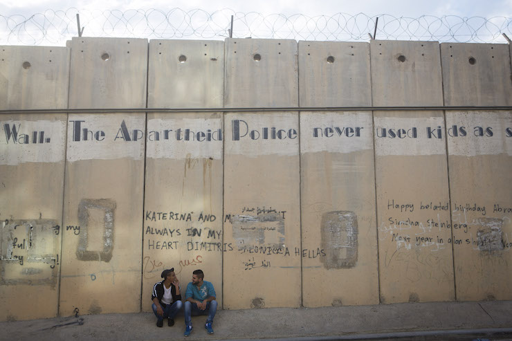 Young Palestinian men sit beneath the separation wall in the West Bank city of Al-Ram, September 29, 2014. (Miriam Alster/Flash90)