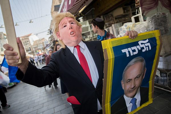 A Likud party supporter wears a Donald Trump mask during a Likud election campaign event at Mahane Yehuda market in Jerusalem, April 7, 2019. (Yonatan Sindel/Flash90)