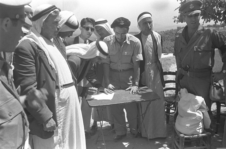 The heads of the Arab city Umm al-Fahm, in the presence of Israeli military officials, sign an oath of allegiance to the State of Israel after the city came under Israeli control in the 1948 war. (GPO)