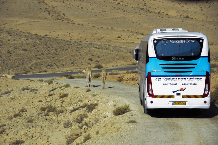 Illustrative photo of an Israeli bus driving along an unpaved road in the Negev/Naqab desert. (Zoe Vayer/Flash90)