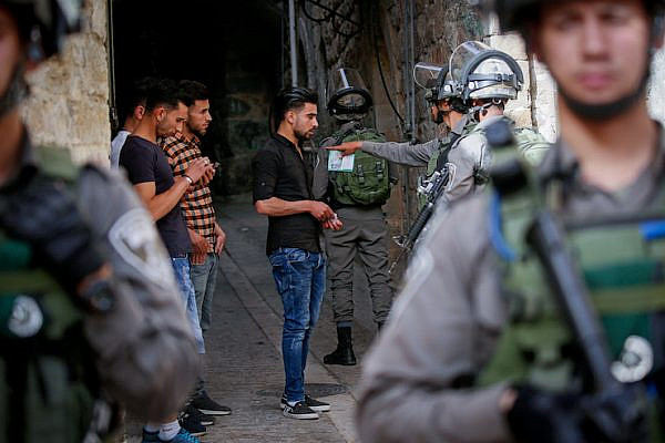 Israeli soldiers check the IDs of Palestinian boys in the Old City of Hebron, West Bank, on May 23, 2018. (Wisam Hashlamoun/Flash90)