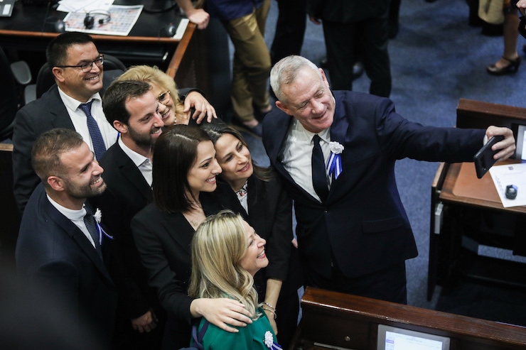 Blue and White chairman Benny Gantz takes a selfie with his colleagues during the swearing-in ceremony of Knesset members as a new session opens following the elections, on April 30, 2019. (Noam Revkin Fenton/Flash90)