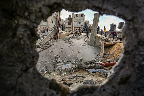 Palestinian walk through the wreckage of a building damaged by Israeli air strikes, Rafah, southern Gaza Strip, May 5, 2019. (Abed Rahim Khatib/Flash90)