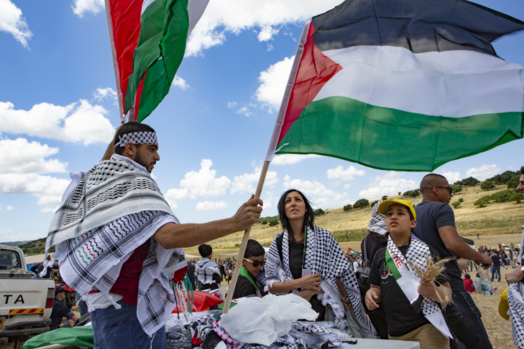 A volunteer hands out Palestinian flags and kaffiyehs to participants at the 22nd annual Return March marking Nakba Day, held this year at the site of the destroyed village of Khubbeiza, May 9, 2019. (Mati Milstein)