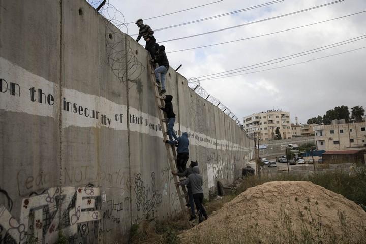 Palestinians climb over the separation wall on the first Friday of Ramadan at Qalandiya checkpoint, West Bank, May 10, 2019. (Oren Ziv/Activestills.org)
