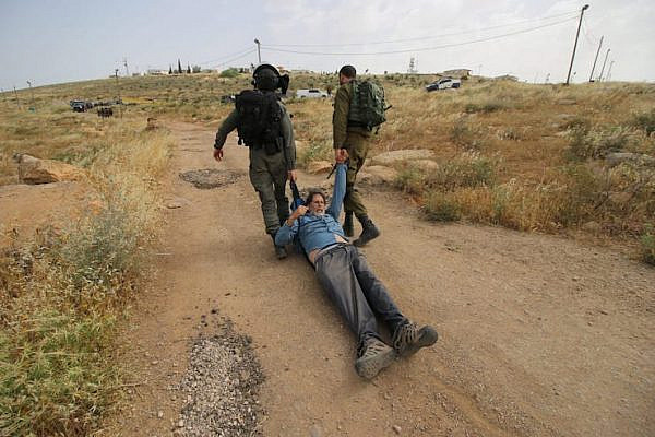 Israeli soldiers violently drag Rabbi Arik Ascherman while he and a group of activists attempt to repair an access road for a cluster of Palestinian villages in the South Hebron Hills on May 3, 2019. (Ahmad al-Bazz/Activestills.org)
