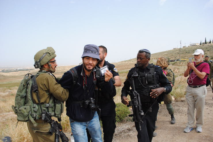 Israeli soldiers arrest photographer Ahmad al-Bazz while he was covering a group of activists attempting to repair an access road for a cluster of Palestinian villages in the South Hebron Hills on May 3, 2019. (Sam Fine)