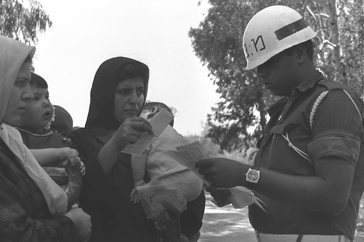 "A military police officer inspects papers belonging to Palestinian women arriving from Jordan via Allenby Bridge, June 24, 1970. (Moshe Milner/GPO) שוטר צבאי במסוף הגבול הישראלי-ירדני, בגשר אלנבי בודק את המסמכים של מבקרים מירדן הבאים לבקר את קרובי משפחתם ביו""ש למשך חודשי הקיץ, במסגרת תוכנית ביקורי קיץ של הממשל הצבאי."