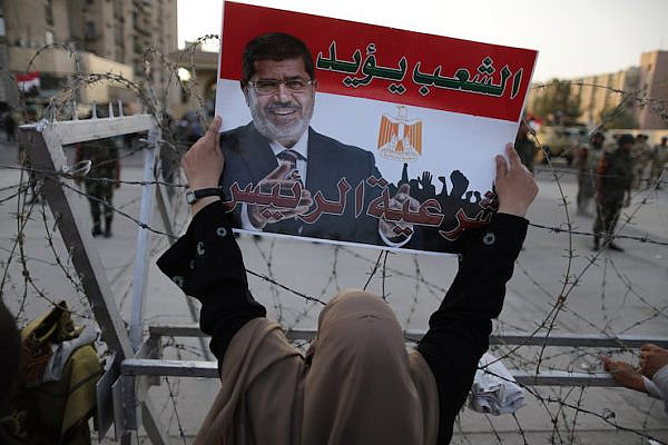 """A supporter of Egypt's ousted president, Mohamed Morsi, holds a poster of him with Arabic writing reading """"The people support the president,"""" Cairo, Egypt, on July 06, 2013. (Wissam Nassar/Flash90)"""