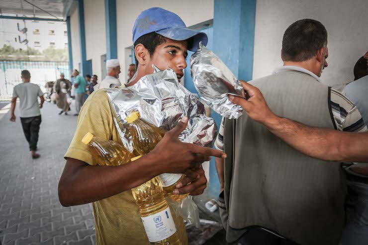 Palestinians receive aid packs from the United Nations Relief and Works Agency for Palestine Refugees (UNWRA) in Rafah, southern Gaza Strip, on September 27, 2018. (Abed Rahim Khatib/Flash90)