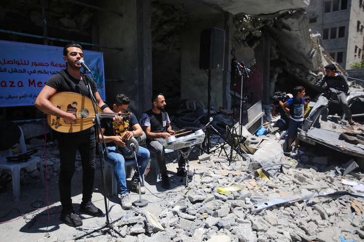 A Palestinian band perform during a concert calling to boycott the Eurovision Song Contest hosted by Israel in Tel Aviv, on the rubble of a building that was recently destroyed by Israeli air strikes in Gaza City on May 14, 2019. (Hassan Jedi/Flash90)