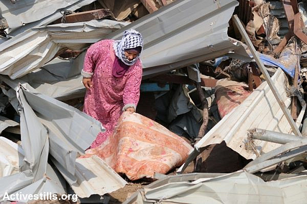 A Palestinian woman examines the damage caused to her house after Israeli forces demolished it, Al Hadidiya, Jordan Valley, West Bank, October 11, 2018. (Ahmad Al-Bazz/Activestills.org)