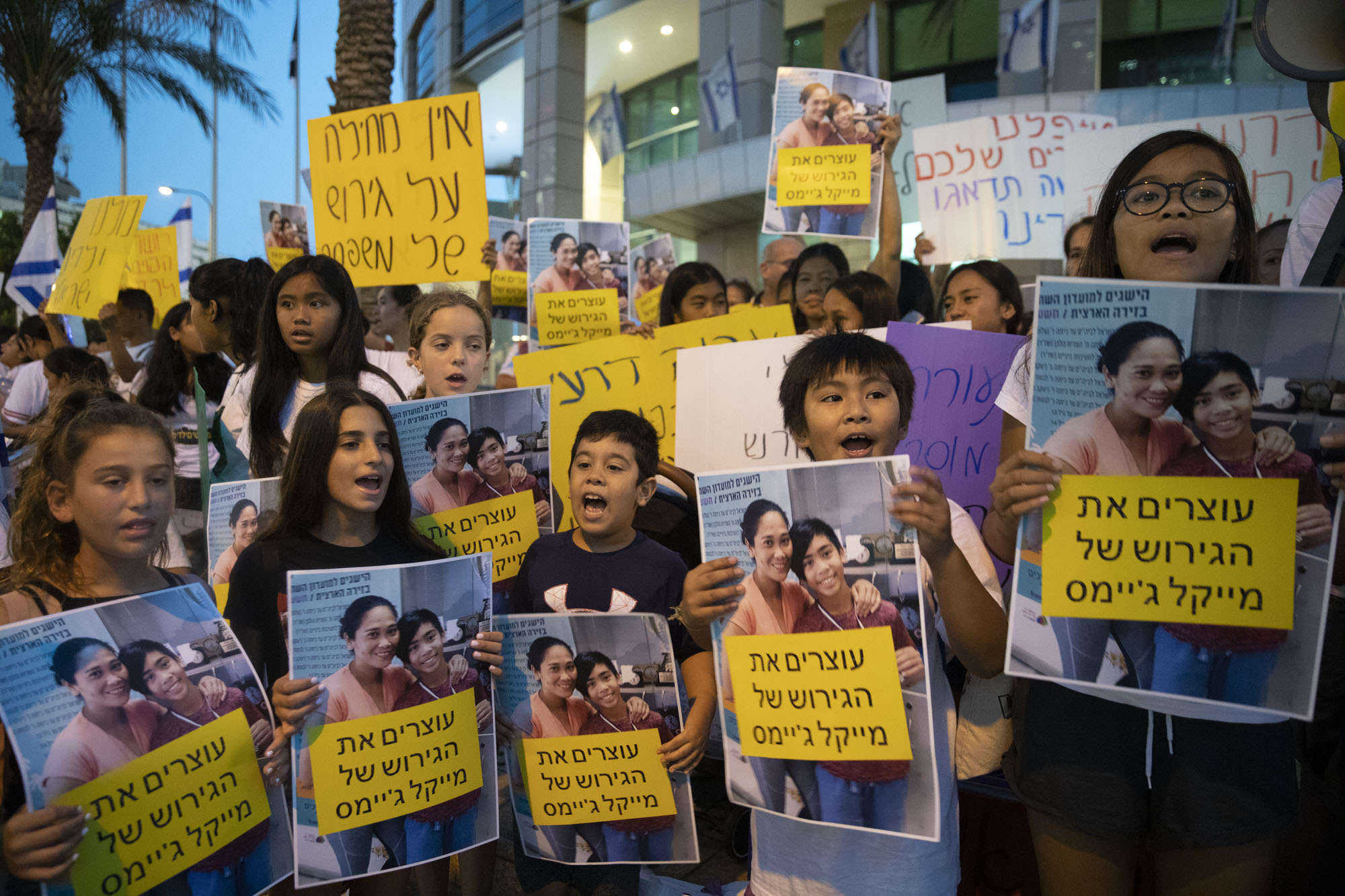 Filipino schoolchildren protest with their classmates against the deportation of foreign workers and their children in front of the Interior Ministry in Tel Aviv. The posters read 'Stopping the deportation of Michael James.' July 22, 2019. (Oren Ziv/Activestills.org)