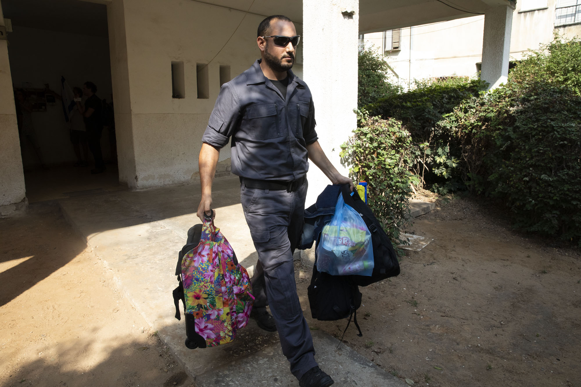 An Israeli immigration officer carries bags from Geraldine Esta's home in Ramat Gan, July 23, 2019. (Oren Ziv/Activestills.org)