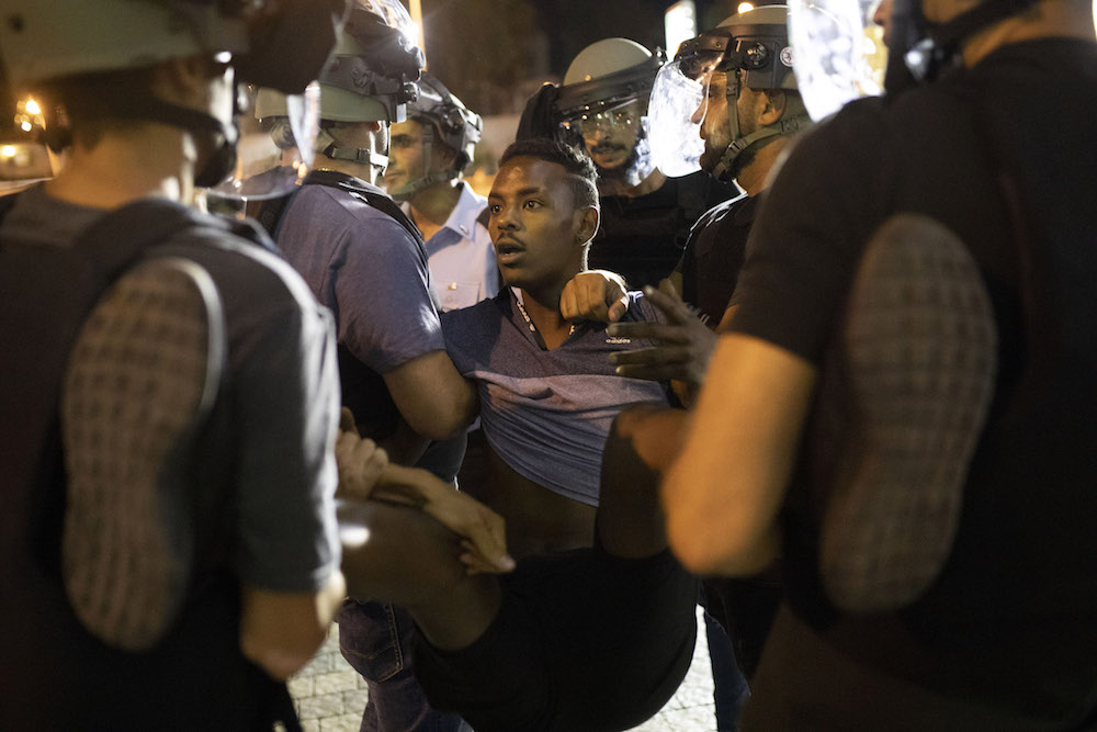 Israeli police remove an Ethiopian-Israeli from a demonstration on Ayalon Highway following the police shooting of Solomon Tekah, July 2, 2019. (Oren Ziv/Activestills.org)