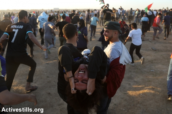 Palestinians evacuate a protester during a Great Return March protest near the Gaza fence, east of Gaza City, November 2, 2018. (Mohammed Zaanoun/Activestills.org)