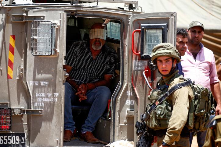 Illustrative photo of Israeli soldiers arresting a Palestinian man in the West Bank, June 23, 2018. (Wisam Hashlamoun/Flash90)