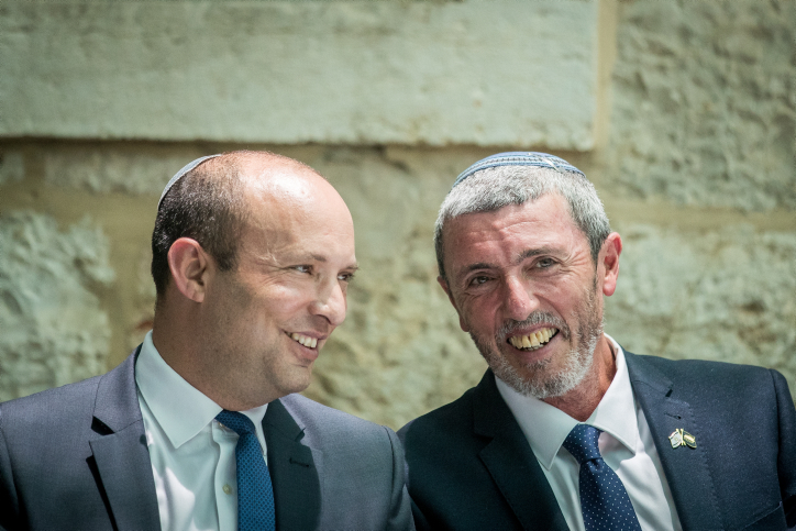 Outgoing Israeli Minister of Education Naftali Bennett speaks with newly appointed Education Minister MK Rafi Peretz, Jerusalem, June 26, 2019. (Yonatan Sindel/Flash90)