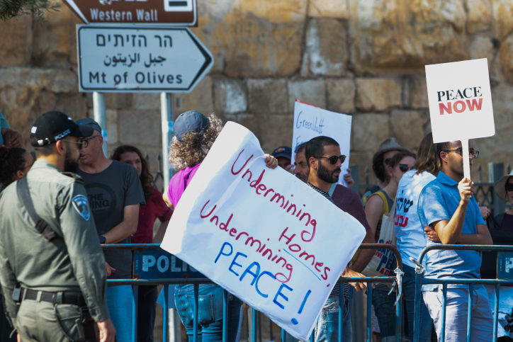 Peace Now activists protest outside the opening of an ancient road at the City of David archaeological site in the East Jerusalem neighborhood of Silwan, June 30, 2019. (Flash90)