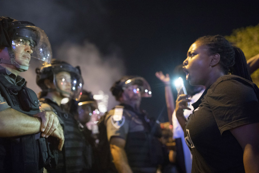 An Ethiopian Israeli woman confronts police officers during a protest by the Ethiopian community against police brutality, following the killing of Solomon Tekah, July 3, 2019. (Oren Ziv/Activestills.org)