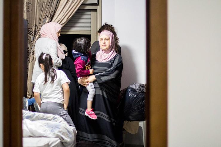 A Palestinian family looks outside the window as soldiers and militarized police arrive to East Jerusalem's Sur Baher area to carry out slated demolitions, July 22, 2019. (Emily Glick)