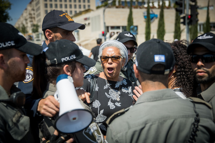 Israeli police surround an Ethiopian Israeli woman at a protest following the police killing of a young black man a few days earlier, Jerusalem, July 15, 2019. (Yonatan Sindel/Flash90)