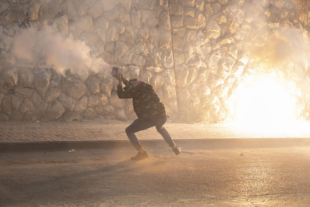 A Palestinian demonstrator launches fireworks during clashes with Israeli police in the East Jerusalem neighborhood of Issawiya, July 1, 2019. (Oren Ziv/Activestills.org)