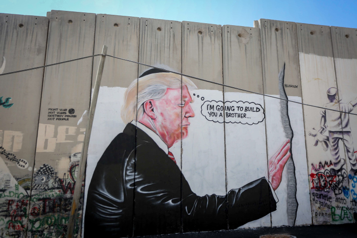 A mural depicting President Donald Trump kissing an Israeli army watchtower is seen on the separation barrier in the West Bank city of Bethlehem, August 4, 2017. (Flash90)