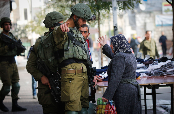 Israeli soldiers argue with a Palestinian woman during clashes at a protest against U.S. President Donald Trump's decision to recognize Jerusalem as the capital of Israel, Hebron, December 10, 2017. (Wisam Hashlamoun/Flash90)