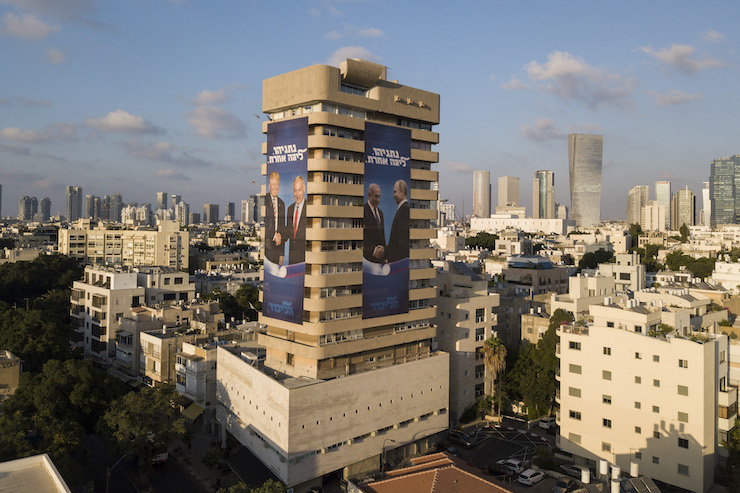 Election campaign posters on the Likud party headquarters building in central Tel Aviv show Prime Minister Benjamin Netanyahu shaking hands with Russian President Vladimir Putin and US President Donald Trump, on July 28, 2019. (Adam Shouldman/Flash90)