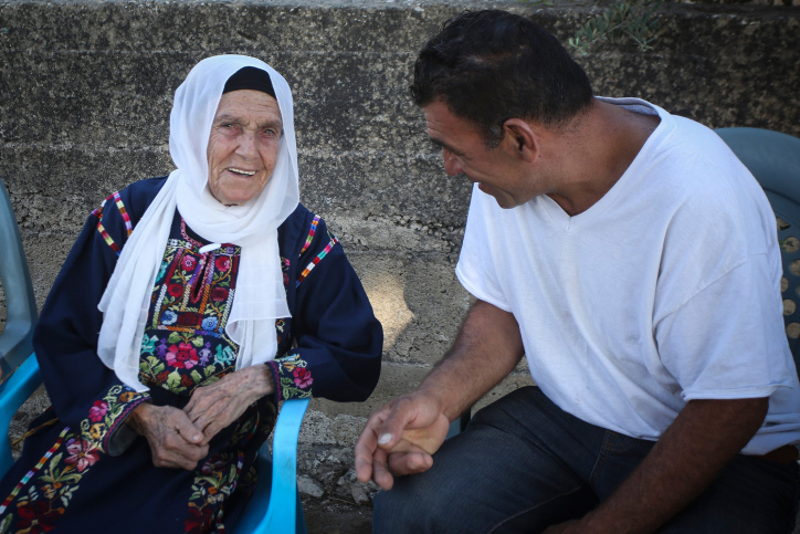 Muftia, the grandmother of U.S. Congresswoman Rashida Tlaib, sits with family members outside her home in the village of Beit Ur Al-Fauqa, West Bank, August 16, 2019. (Flash90)